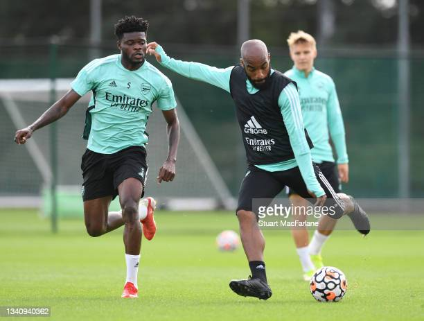 Thomas Partey and Alex Lacazette of Arsenal during a training session at London Colney on September 17, 2021 in St Albans, England.
