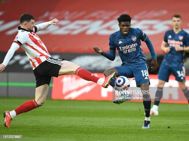 Thomas Partey of Arsenal challenged by Oli Burke of Sheffield United during the Premier League match between Sheffield United and Arsenal at Bramall...