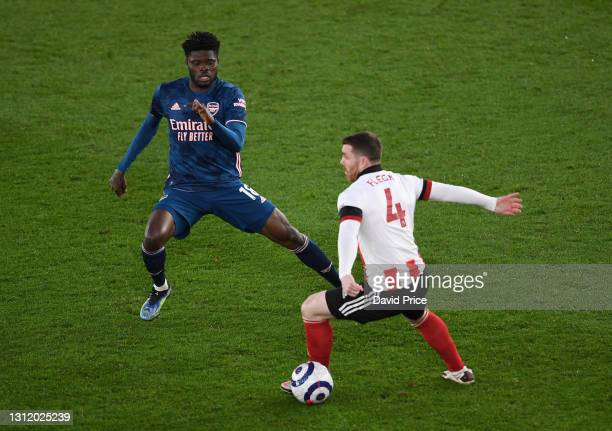 Thomas Partey of Arsenal closes down John Fleck of Sheffield United during the Premier League match between Sheffield United and Arsenal at Bramall...