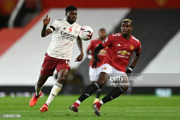 Thomas Partey of Arsenal is put under pressure by Paul Pogba of Manchester United during the Premier League match between Manchester United and...