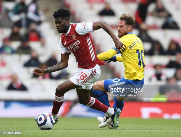 Thomas Partey of Arsenal takes on Alexis MacAllister of Brighton during the Premier League match between Arsenal and Brighton & Hove Albion at...