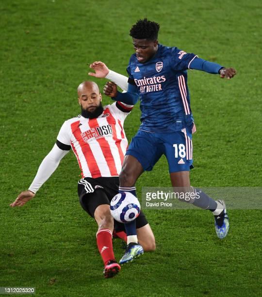 Thomas Partey of Arsenal takes on David McGoldrick of Sheffield United during the Premier League match between Sheffield United and Arsenal at...