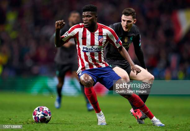 Thomas Partey of Atletico de Madrid competes for the ball with Andrew Robertson of Liverpool FC during the UEFA Champions League round of 16 first...
