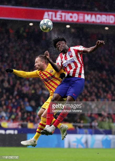 Thomas Partey of Atletico Madrid and Arthur of FC Barcelona jump for a header during the Liga match between Club Atletico de Madrid and FC Barcelona...
