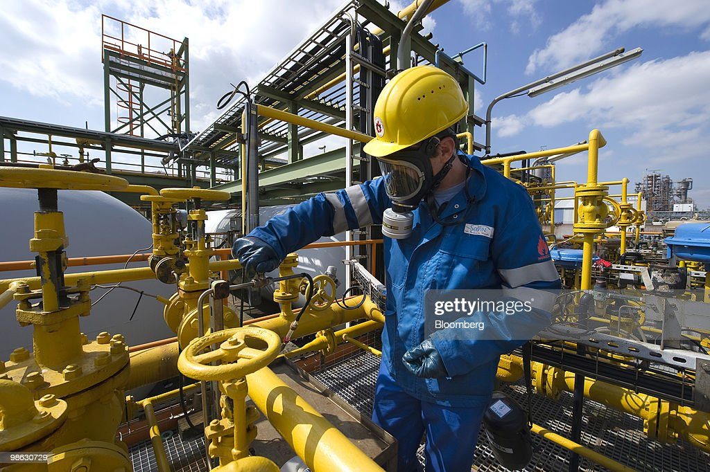 Thomas Pauwels, a chemist with Solvay SA, takes a sample of liquid chlorine at the company's chemical plant in Antwerp, Belgium, on Thursday, April 22, 2010. Confidence within Europe�s chemical industry has risen for the first time in 21 months, ICIS news reported, citing data from the European Chemical Industry Council. Photographer: Jock Fistick/Bloomberg via Getty Images