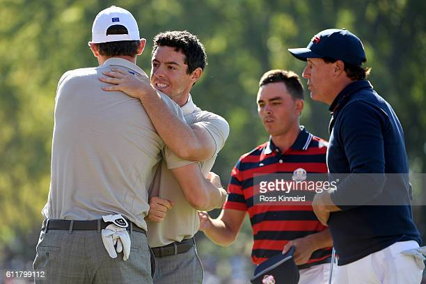 Thomas Pieters and Rory McIlroy of Europe react after winning their match on the 16th green with Rickie Fowler and Phil Mickelson of the United...