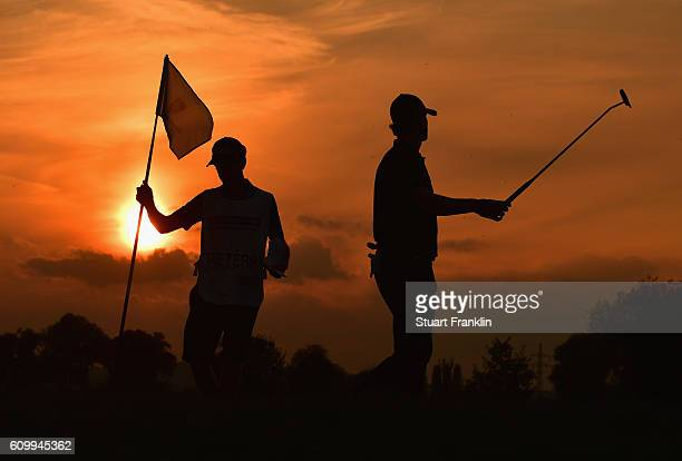Thomas Pieters of Belgium and his caddie looks on as the sun sets during the second round on day two of the Porsche European Open at Golf Resort Bad...