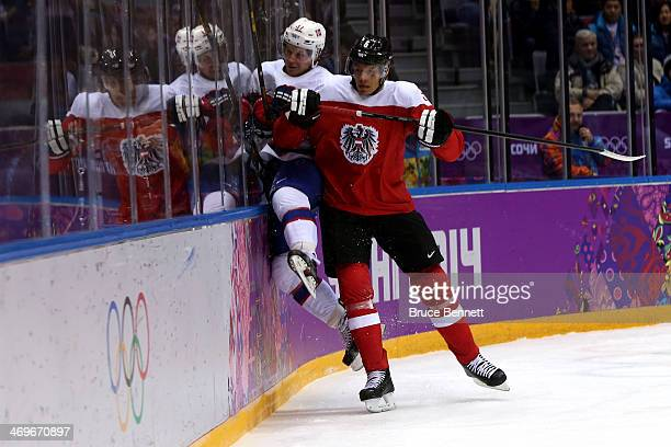 Thomas Raffl of Austria checks Patrick Thoresen of Norway during the Men's Ice Hockey Preliminary Round Group B game on day nine of the Sochi 2014...
