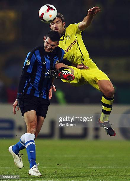 Thomas Rathgeber of Saarbruecken is challenged by Sokratis Papastathopoulos of Dortmund during the DFB Cup Round of 16 match between 1 FC...