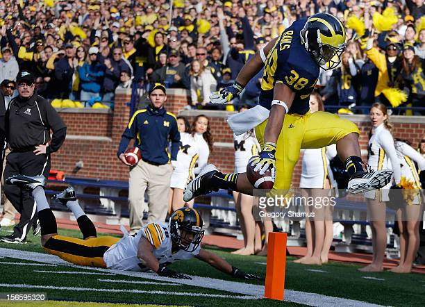 Thomas Rawls of the Michigan Wolverines tries to break the plan of the end zone during a second quarter run in front of Micah Hyde of the Iowa...