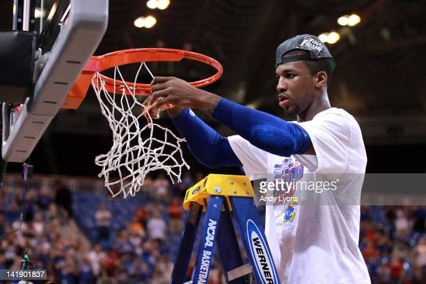 Thomas Robinson of the Kansas Jayhawks cuts down a piece of the net in celebration of winning 80-67 against the North Carolina Tar Heels during the...