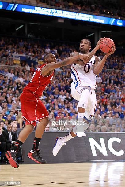 Thomas Robinson of the Kansas Jayhawks drives for a shot attempt in the first half against CJ Williams of the North Carolina State Wolfpack during...