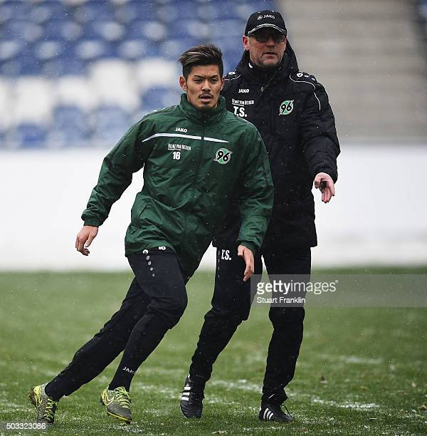 Thomas Schaaf head coachof Hannover 96 gives instructions to new signing Hotaru Yamaguchi during his first training session after the announcement of...