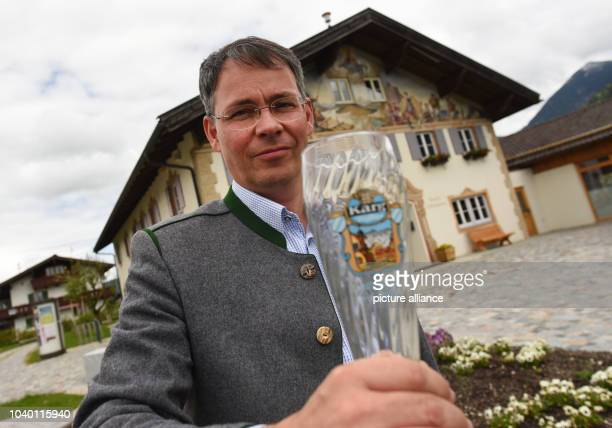 Thomas Schwarzenberger, Mayor of Kruen, sitting in front of the town hall in Kruen, Germany, 20 May 2016. Schwarzenberger is holding the beer glass...