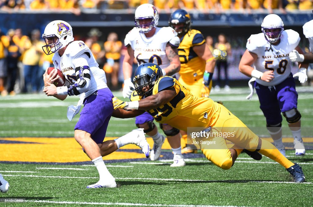 Thomas Sirk #10 of the East Carolina Pirates avoids a tackle by Xavier Pegues #99 of the West Virginia Mountaineers during the first quarter at Mountaineer Field on September 9, 2017 in Morgantown, West Virginia.