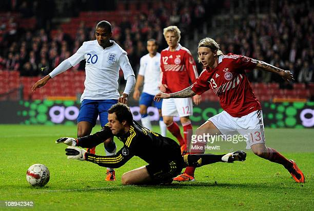 Thomas Sorensen of Denmark claims the ball under pressure from Ashley Young of England during the International Friendly match between Denmark and...