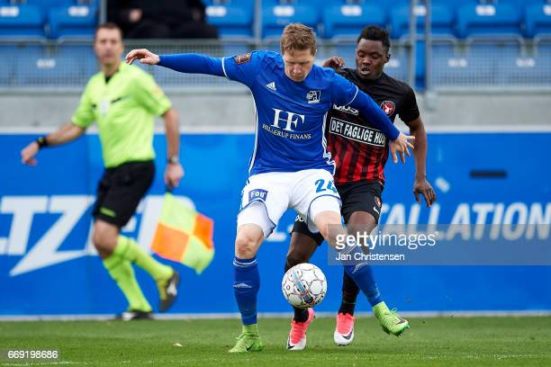 Thomas Sorensen of Lyngby BK and Rilwan Hassan of FC Midtjylland compete for the ball during the Danish Alka Superliga match between Lyngby BK and FC...