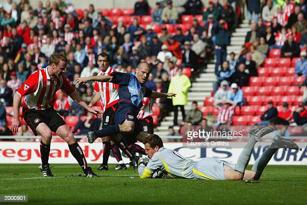 Thomas Sorensen of Sunderland has to be brave as he holds onto the ball as Fredrik Ljungberg of Arsenal comes crashing in during the FA Barclaycard...