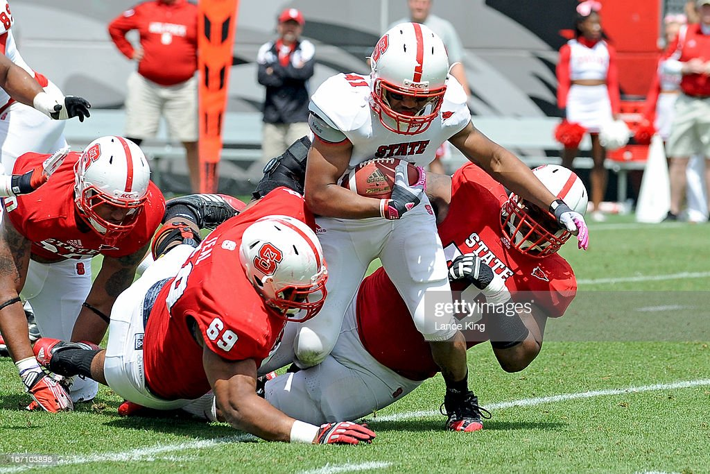 Thomas Teal #69 and T.Y. McGill #75 tackle Milton Hall #41 of the North Carolina State Wolfpack during the Kay Yow Spring Football Game at Carter-Finley Stadium on April 20, 2013 in Raleigh, North Carolina.