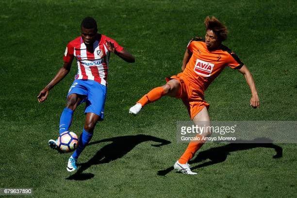 Thomas Teye Partey of Atletico de Madrid competes for the ball with Takashi Inui of SD Eibar during the La Liga match between Club Atletico de Madrid...