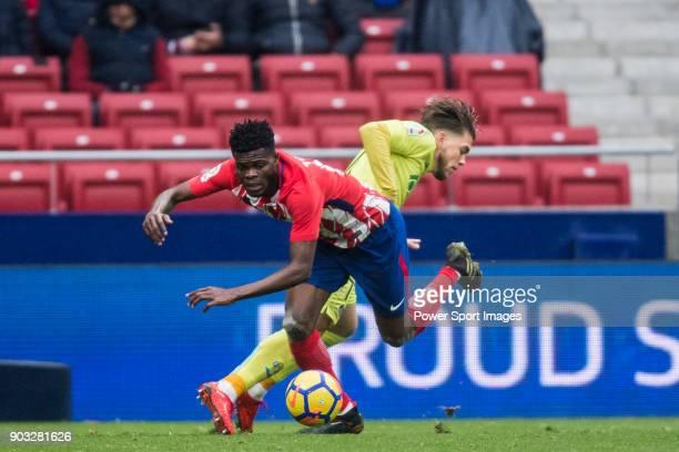 Thomas Teye Partey of Atletico de Madrid competes for the ball with Alvaro Jose Jimenez Guerrero of Getafe CF during the La Liga 201718 match between...