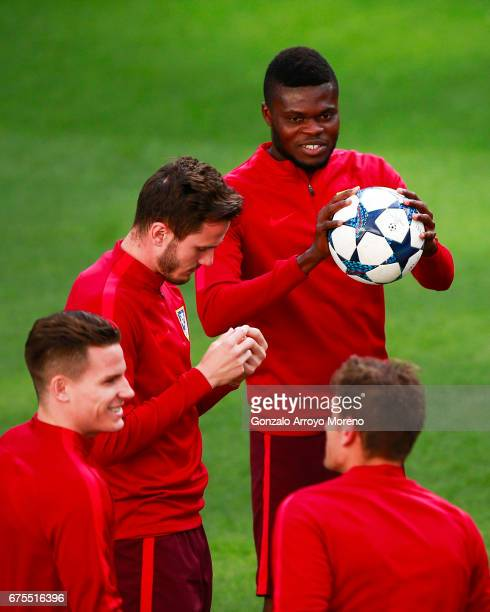 Thomas Teye Partey of Atletico de Madrid holds the ball behind his teammates Kevin Gameiro and Saul Niguez during a training session ahead of the...