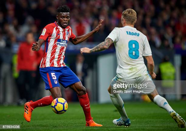 Thomas Teye Partey of Atletico Madrid competes for the ball with Toni Kroos of Real Madrid during the La Liga match between Atletico Madrid and Real...