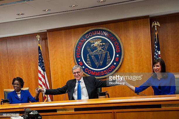 Thomas 'Tom' Wheeler chairman of the Federal Communications Commission center holds hands with commissioners Mignon Clyburn left and Jessica...