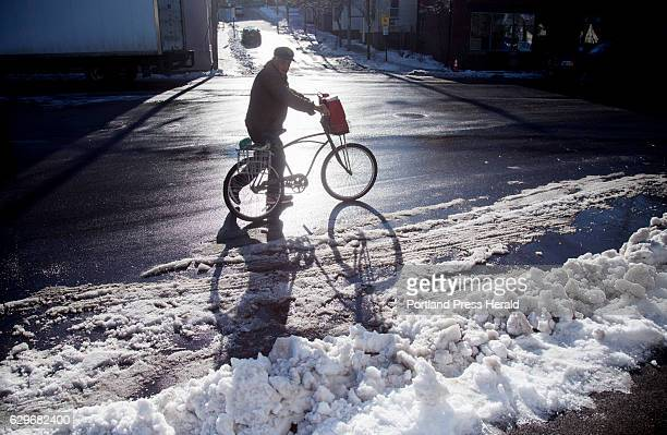 Thomas Trott of Portland walks his bicycle along an icy section of Portland Street after grocery shopping Tuesday morning Thomas says he bikes...