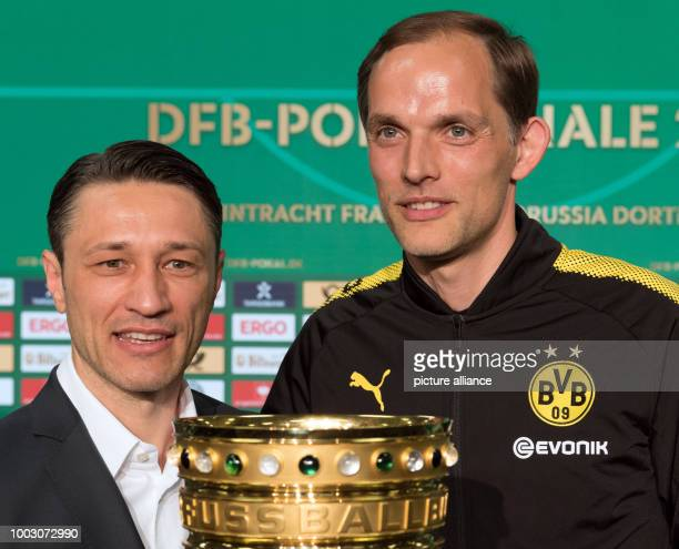Thomas Tuchel head coach of German Bundesliga soccer club Borussia Dortmund and his Eintracht Frankfurt counterpart Niko Kovac seen behind the trophy...