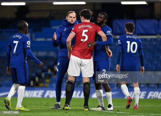 Thomas Tuchel, Manager of Chelsea interacts with Harry Maguire of Manchester United and Antonio Rudiger of Chelsea following the Premier League match...