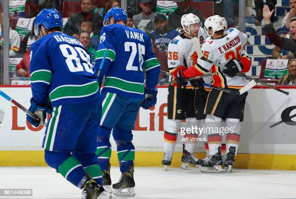 Thomas Vanek and Sam Gagner of the Vancouver Canucks look on as Freddie Hamilton and Troy Brouwer of the Calgary Flames celebrate a Calgary goal...