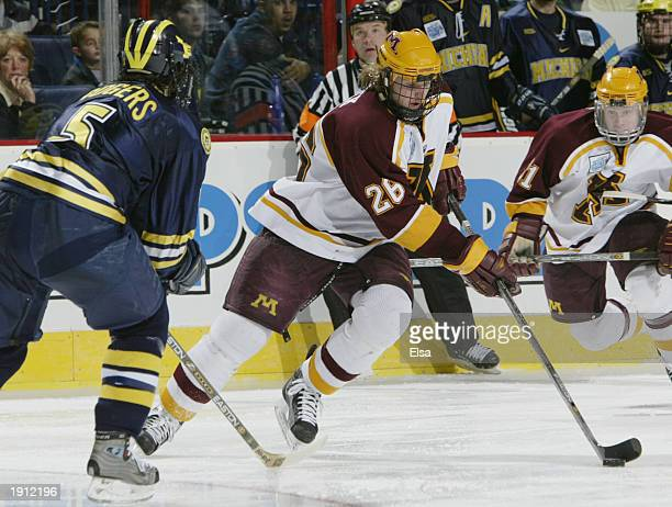 Thomas Vanek of Minnesota takes the puck past Brandon Rodgers of Michigan during the NCAA Frozen Four on April 10, 2003 at the HSBC Arena in Buffalo,...