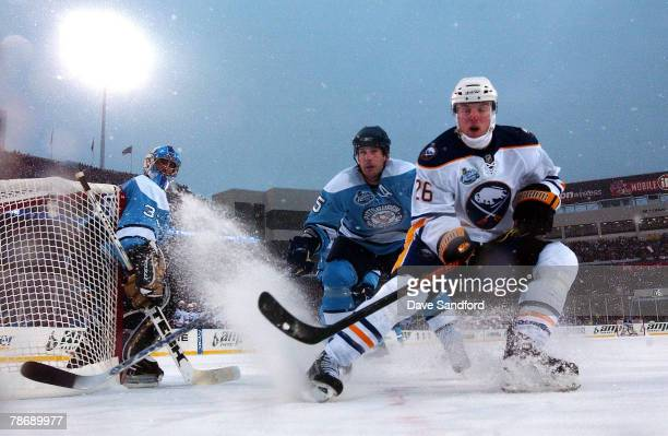 Thomas Vanek of the Buffalo Sabres and Darryl Sydor of the Pittsburgh Penguins chase the puck past goaltender Ty Conklin during the NHL Winter...