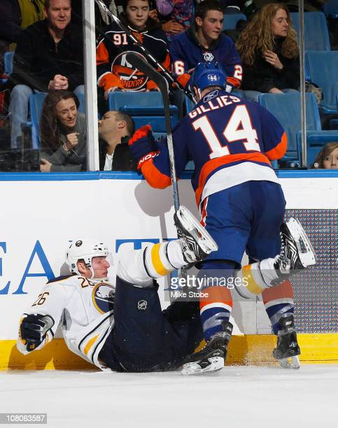 Thomas Vanek of the Buffalo Sabres is knocked to the ice by Trevor Gillies of the New York Islanders on January 15, 2011 at Nassau Coliseum in...
