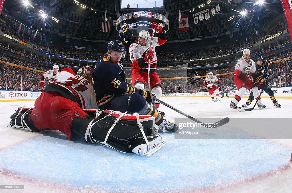 Thomas Vanek #26 of the Buffalo Sabres looks for the puck while falling on goaltender Dan Ellis #31 of the Carolina Hurricanes as Jamie McBain #4 defends on January 25, 2013 at the First Niagara Center in Buffalo, New York.