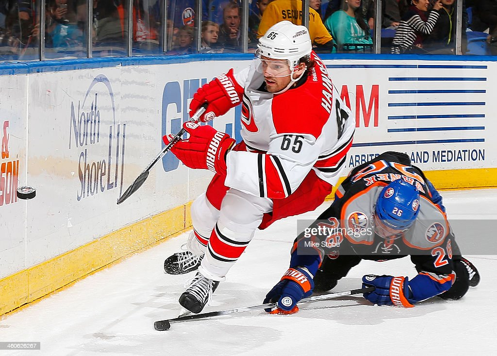 Thomas Vanek #26 of the New York Islanders falls to the ice as Ron Hainsey #65 of the Carolina Hurricanes pursues the puck at Nassau Veterans Memorial Coliseum on January 4, 2014 in Uniondale, New York. The Hurricanes defeated the Islanders 3-2.