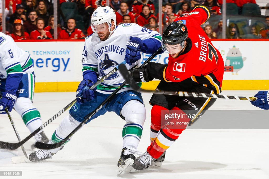 Thomas Vanek #26 of the Vancouver Canucks and TJ Brodie #7 battle for position in a NHL game against the Vancouver Canucks at the Scotiabank Saddledome on December 09, 2017 in Calgary, Alberta, Canada.