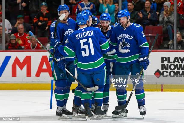 Thomas Vanek of the Vancouver Canucks celebrates with teammates Brock Boeser and Sam Gagner after a Vancouver goal during their NHL game against the...