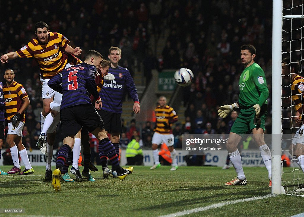 Thomas Vermaelen of Arsenal heads past Bradford goalkeeper Matt Duke to score the Arsenal goal during the Capital One Cup match between Arsenal and Bradford City at Coral Windows Stadium, Valley Parade on December 11, 2012 in Bradford, England.