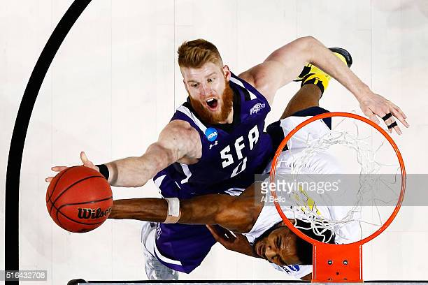 Thomas Walkup of the Stephen F Austin Lumberjacks shoots against Elijah Macon of the West Virginia Mountaineers in the second half during the first...
