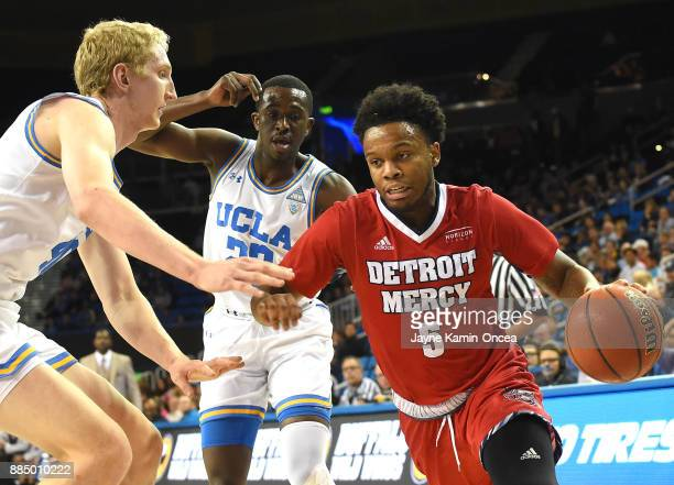Thomas Welsh and Prince Ali of the UCLA Bruins guard Corey Allen of the Detroit Mercy Titans as he drives to the basket in the first half of the game...