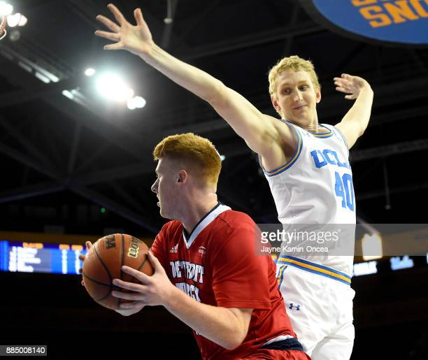 Thomas Welsh of the UCLA Bruins defends Jack Ballantyne of the Detroit Mercy Titans as he drives to the basket in the first half of the game against...