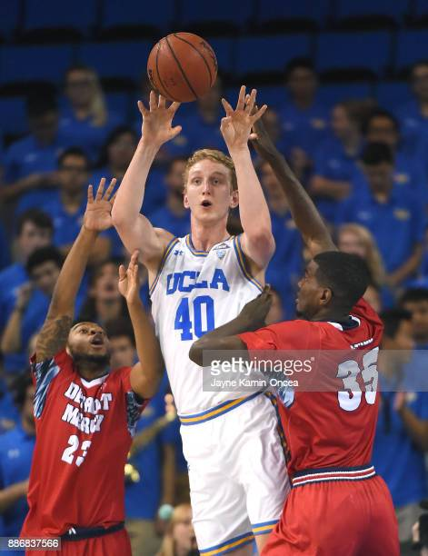 Thomas Welsh of the UCLA Bruins is pressured by Josh McFolley and Gerald Blackshear Jr #25 of the Detroit Mercy Titans as he makes a pass in the game...