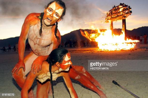 Thomas Wood and his companion artists based in California perform in front a wood structure set in fire at Black Rock City's Burning Man festival in...