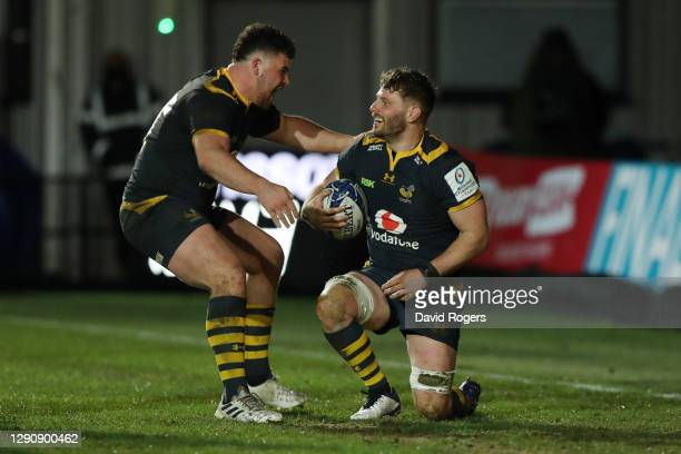 Thomas Young of Wasps celebrates with Alfie Barbeary after scoring their fourth try during the Heineken Champions Cup Pool 1 match between Dragons...