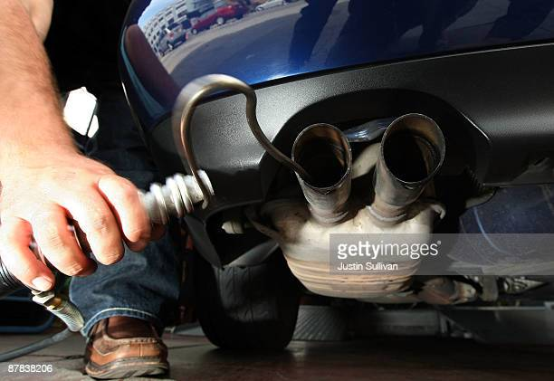 Thomas Zielin inserts a probe into the tailpipe of a car while performing an emissions test at Smog Queen May 18 2009 in San Francisco California The...