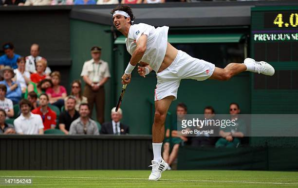 Thomaz Bellucci of Brazil serves during his Gentlemen's Singles first round match against Rafael Nadal of Spain on day two of the Wimbledon Lawn...