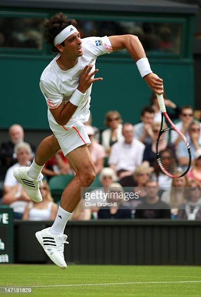 Thomaz Bellucci of Brazil serves during his his Gentlemen's Singles first round match against Rafael Nadal of Spain on day two of the Wimbledon Lawn...