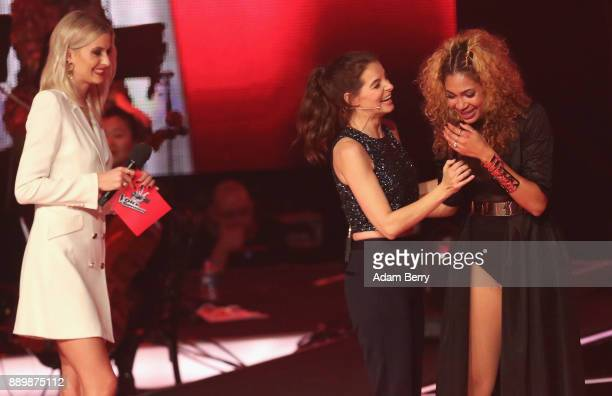 Thomaz reacts next to Yvonne Catterfeld and Lena Gercke as the former wins the 'The Voice of Germany' semifinals at Studio Berlin Adlershof on...